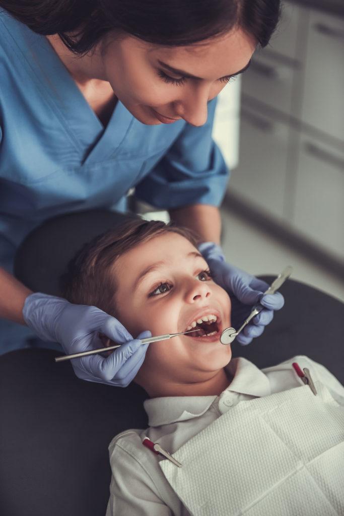 Un petit garçon avec une dentiste sourit.