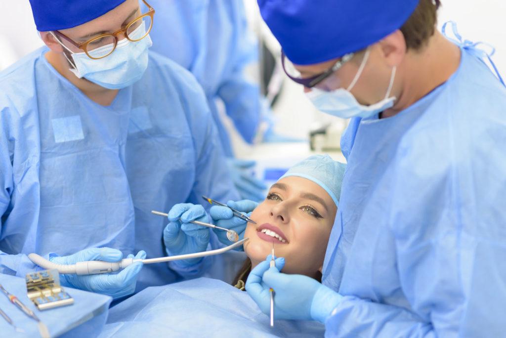 Patiente avec deux dentistes pour une chirurgie dentaire.