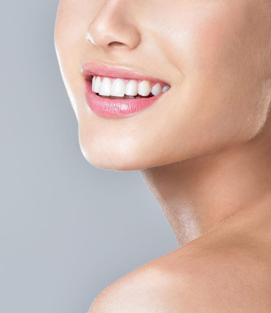 Une femme sourit après des soins dentaires.