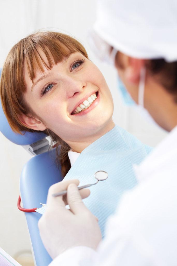 Une femme dans un cabinet dentaire écoute un dentiste et sourit.